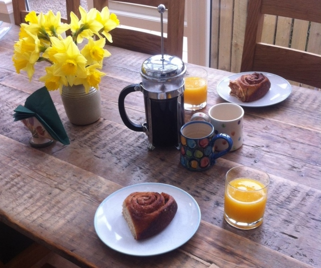 Breakfast table with cinnamon and cardamom buns, coffee, orange juice and daffodils