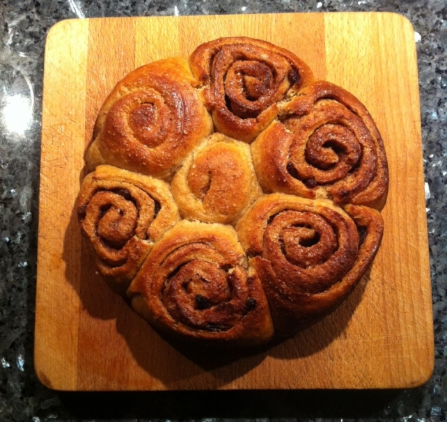 Cinnamon and cardamom buns displayed on a wooden board