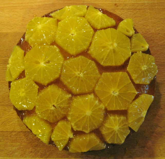 Sponge cake topped with orange slices and syrup on a wooden board