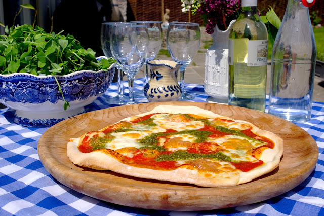Homemade pizza topped with fresh pesto, served on blue crockery with white wine and salad