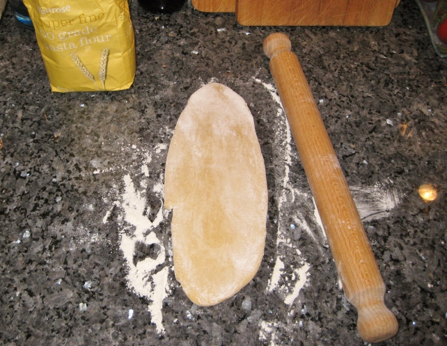 Half the pasta dough rolled into an oblong shape on a floured surface using a rolling pin