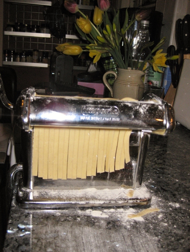 Using the pasta machine to cut the pasta into tagliatelle