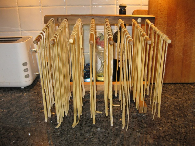 Homemade tagliatelle hanging from a wooden pasta drier