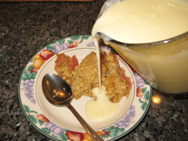 Pouring homemade custard over rhubarb crumble