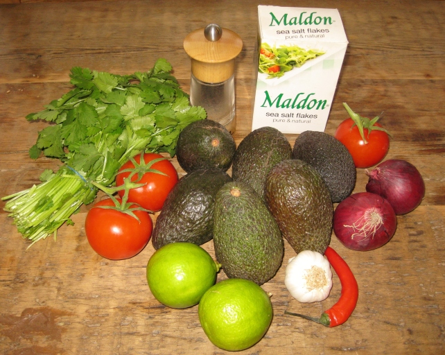 Ingredients for homemade guacamole- avocados, tomatoes, onions, garlic, chilli, lime, coriander, salt and pepper