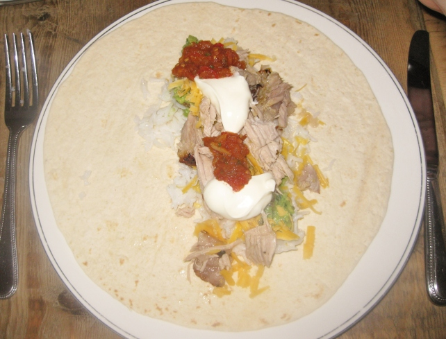 Tortilla wrap with Puerco en Naranja, rice, cheese, guacamole, salsa and sour cream