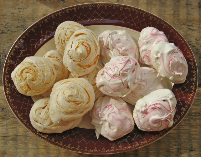 Colourful swirled meringues flavoured with orange and raspberry arranged on a platter
