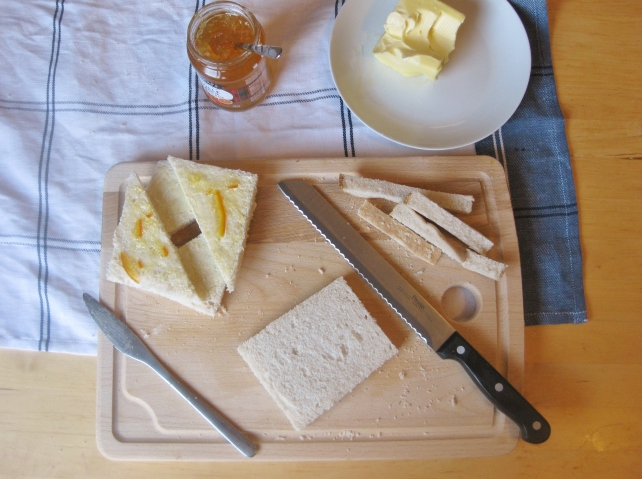 Cutting the crusts off the bread and spreading with butter and marmalade for bread and butter pudding