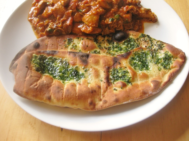 Homemade garlic and coriander naan breads served with chicken and mushroom curry