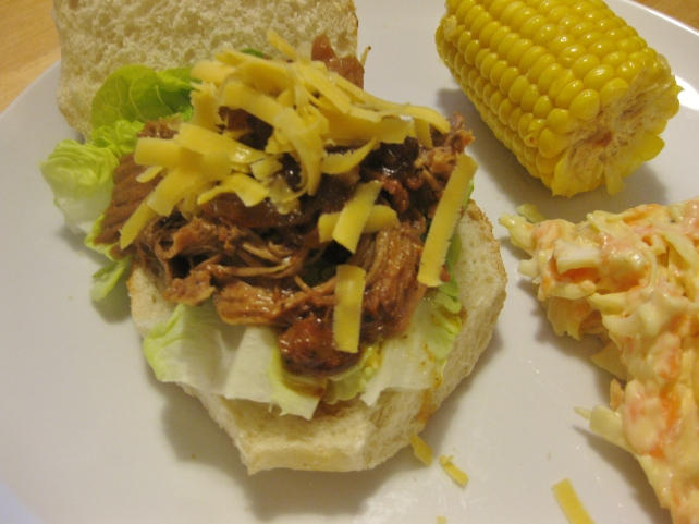 Slow-cooked BBQ pulled pork tagine on a crusty roll served with cheese, coleslaw and corn on the cob
