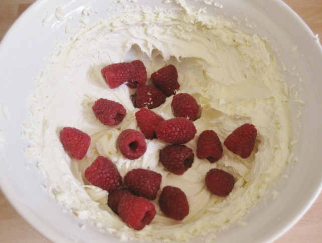 Adding fresh raspberries to the butter cream icing