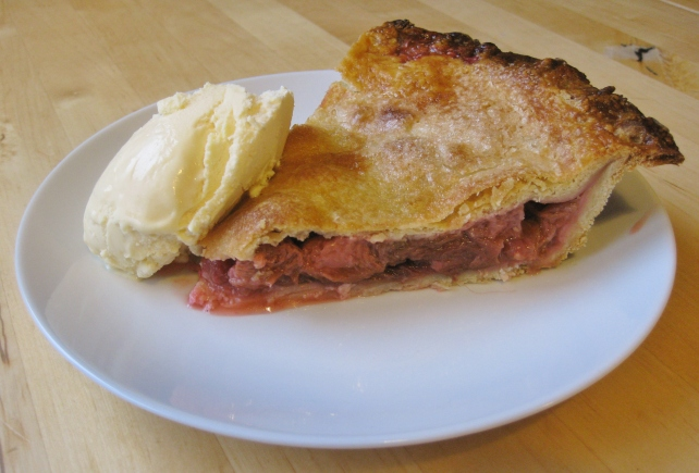 Slice of homemade rhubarb and strawberry pie with ice cream