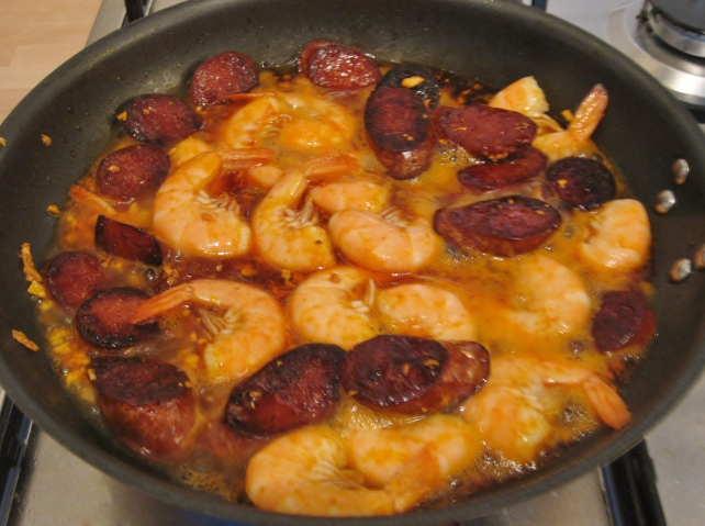Adding the prawns and white wine to the Spanish chorizo and garlic