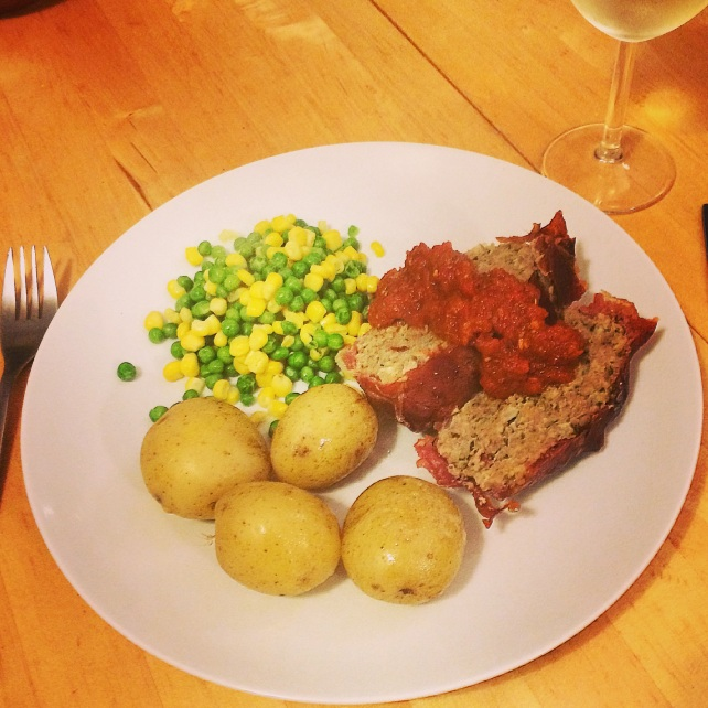 Sunday dinner of meatloaf, homemade tomato sauce, steamed potatoes and vegetables