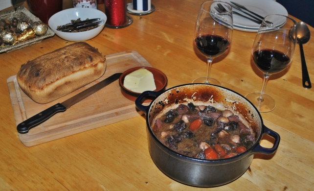 Beef shin and mushroom casserole served with homemade bread and red wine