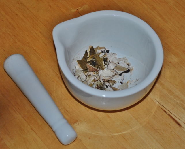 Dried ceps lightly crushed in a pestle and mortar