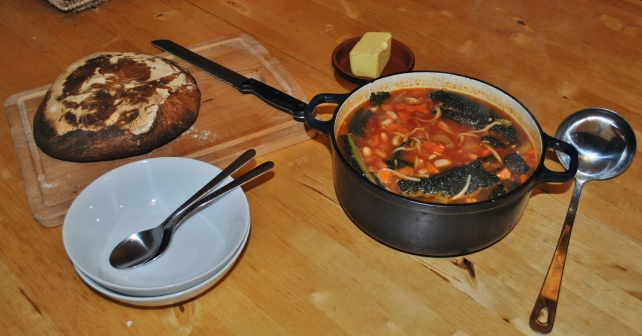 Homemade hearty minestrone soup served with sourdough bread and butter