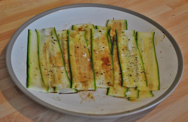 Thinly sliced courgette marinading in oil and balsamic vinegar