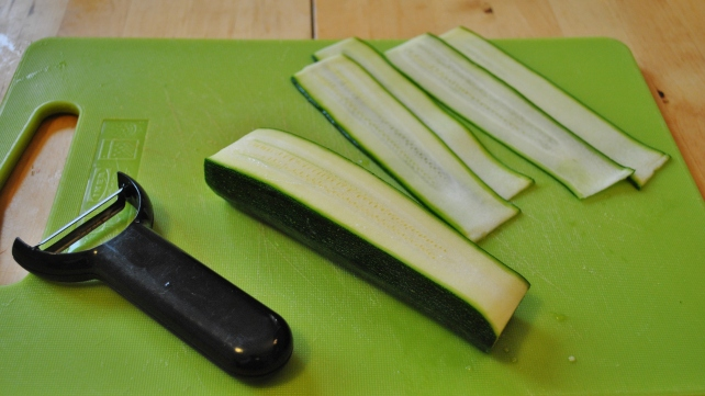 Thinly slicing the courgettes with a vegetable peeler