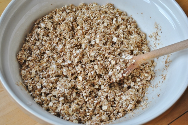 Adding the liquids to the oats for homemade fruit and nut granola