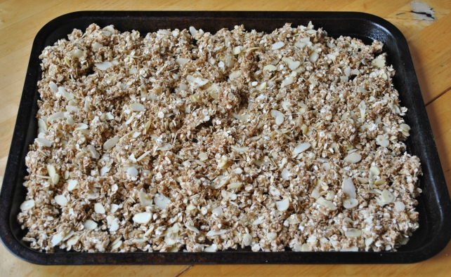 Spreading the granola mixture on a tray for baking