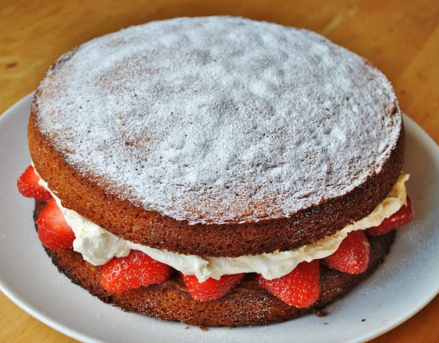 Dusting the Victoria sponge cake with icing sugar