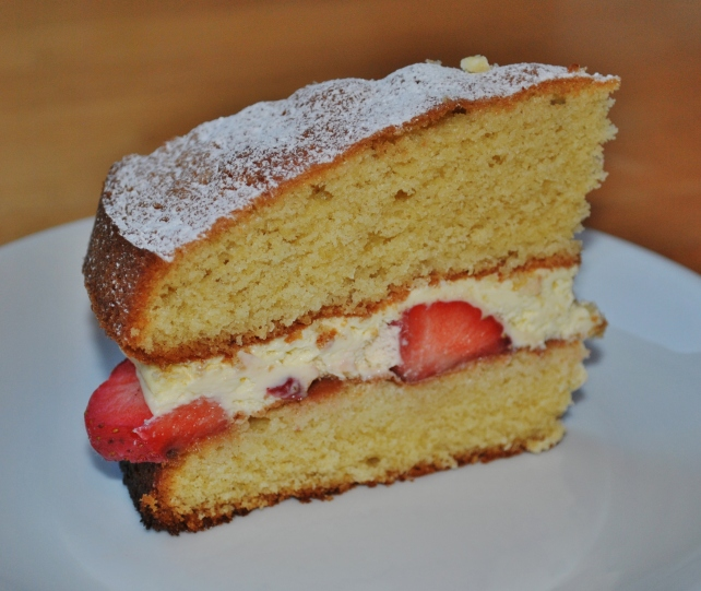 Slice of Victoria sponge cake with strawberries and cream