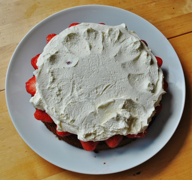 Spreading the whipped double cream on the strawberries
