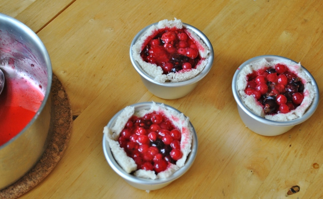Filling the bread lined pudding basins with summer berries