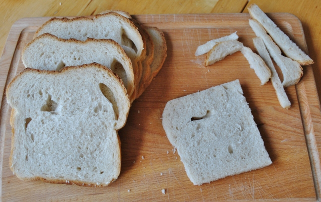Removing the crusts from slices of stale white bread