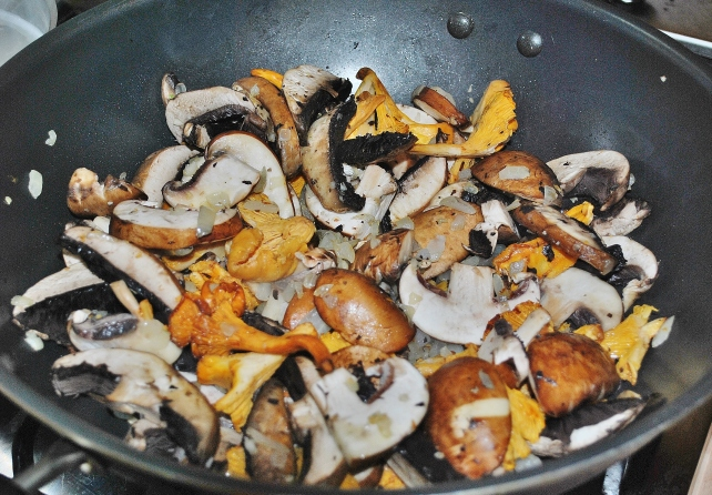 Adding mixed mushrooms to the onions and garlic