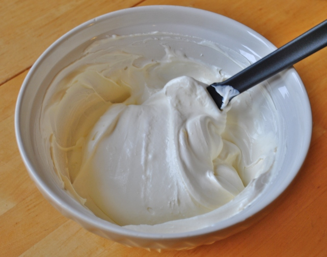 Folding lemon curd through the whipped cream and yogurt mix
