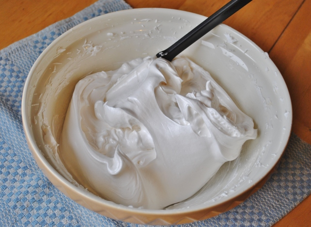 Whisking caster sugar, vanilla, corn flour and vinegar into egg whites for pavlova